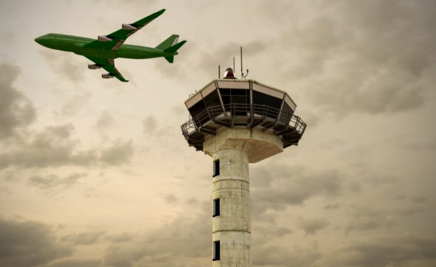 How-to-become-an-air-traffic-controller-plane-flying-past-aviation-tower
