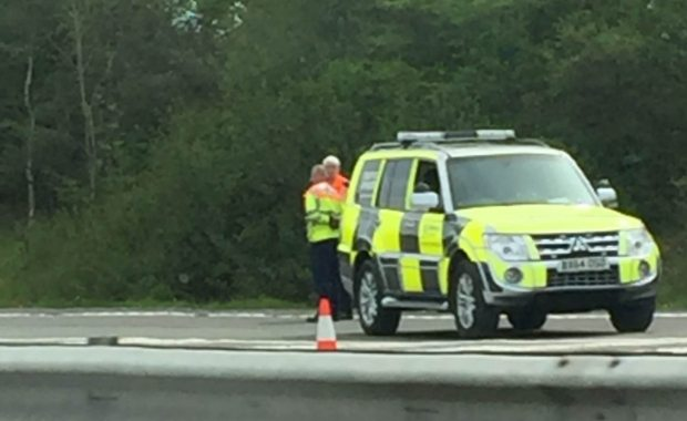 How-to-become-a-traffic-officer-standing-next-to-car