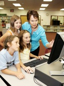A teacher instructing kids on using the computer.