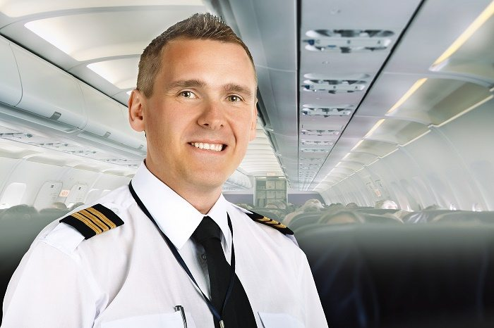 Airline pilot wearing uniform with epaulettes on board of passen