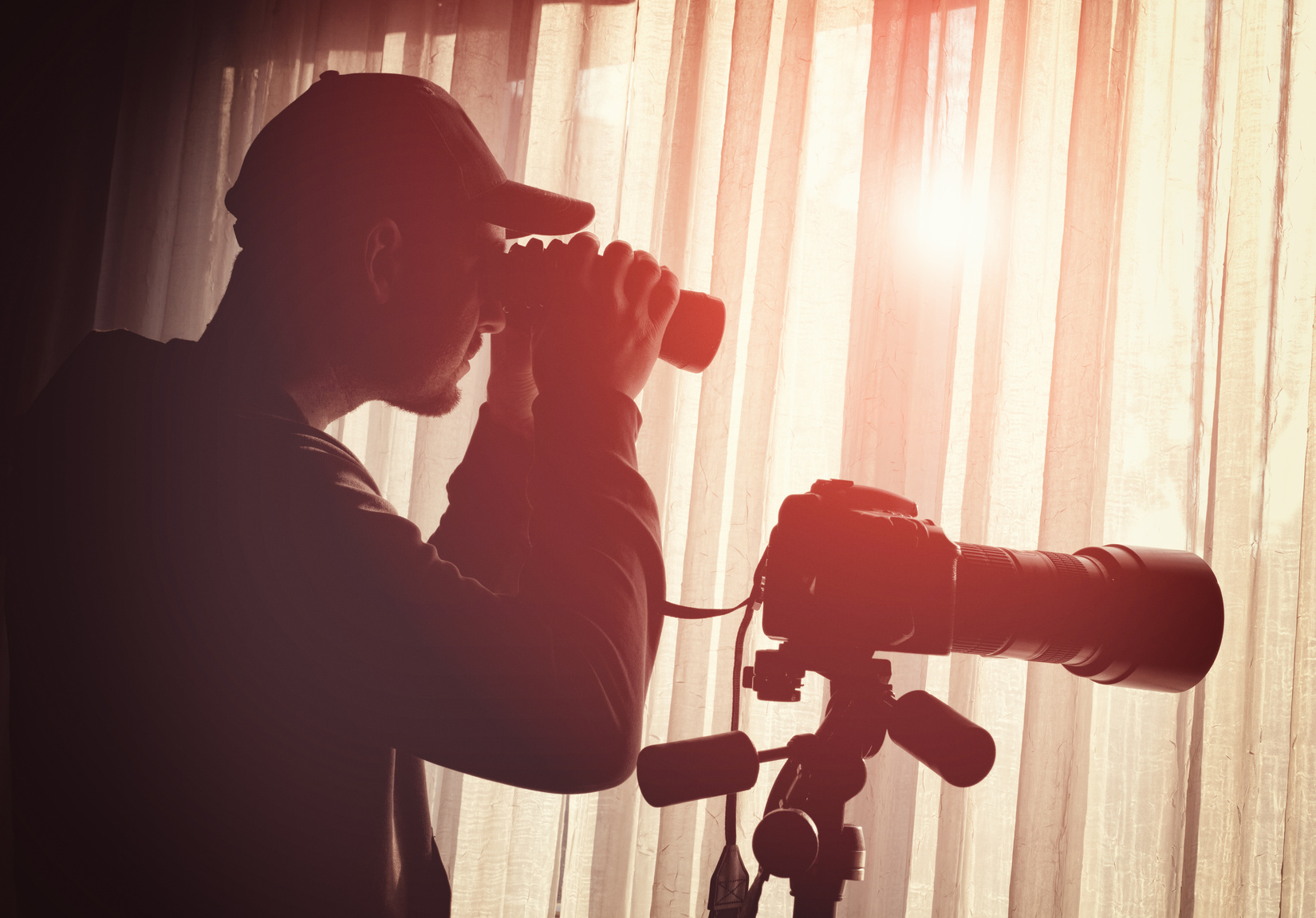 man with binoculars and camera control someone